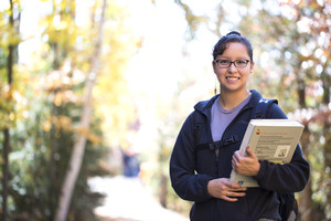 Female student holding books on path going to class