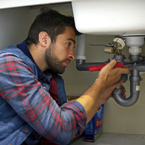 Plumber fixing piping under sink