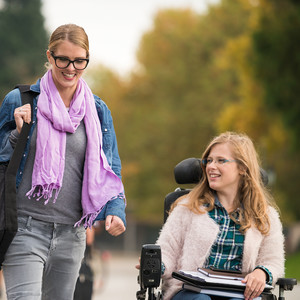 Girl walking and girl in wheelchair on campus