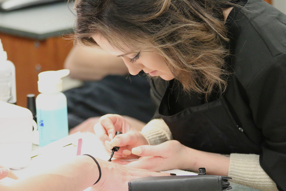 female student working on a manicure