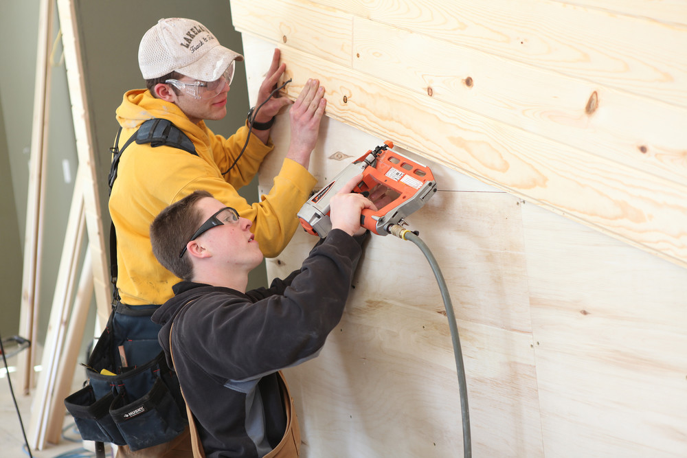 Carpentry apprentice students nailing wood paneling