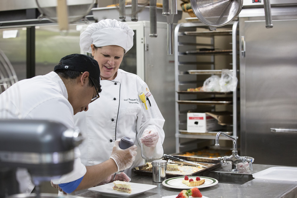 Culinary instructor helping student
