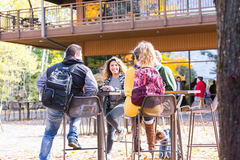 Students sitting at patio in fall