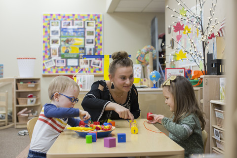 young boy and girl playing at daycare table with student teacher