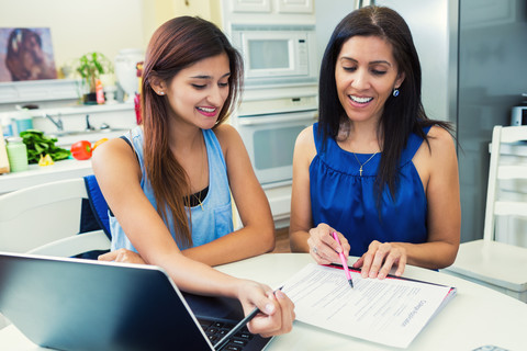 Mother and daughter sitting at kitchen table reviewing homework